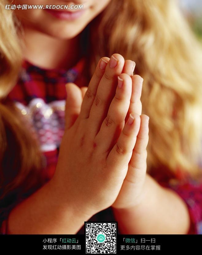 双手合十的金发女孩特写图片