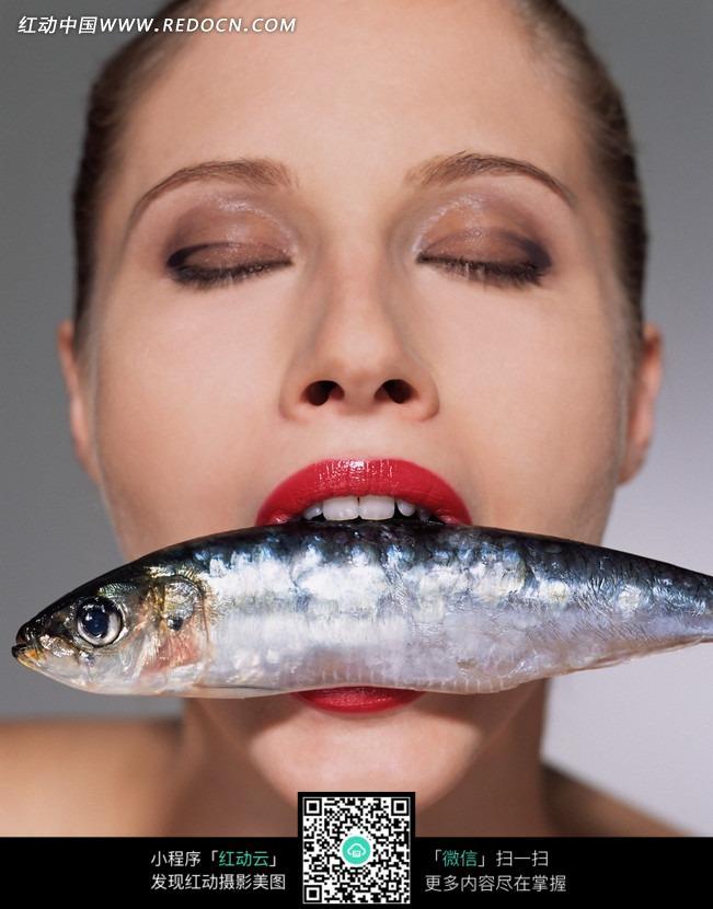 闭着眼睛咬住鱼的美女图片