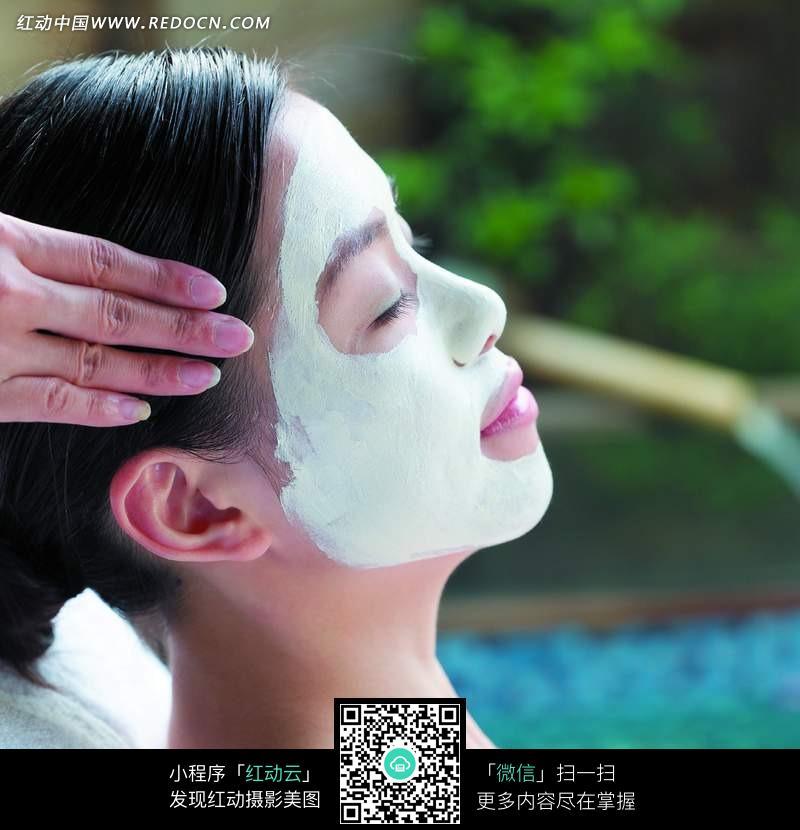 脸敷面膜接受头部按摩的美女图片