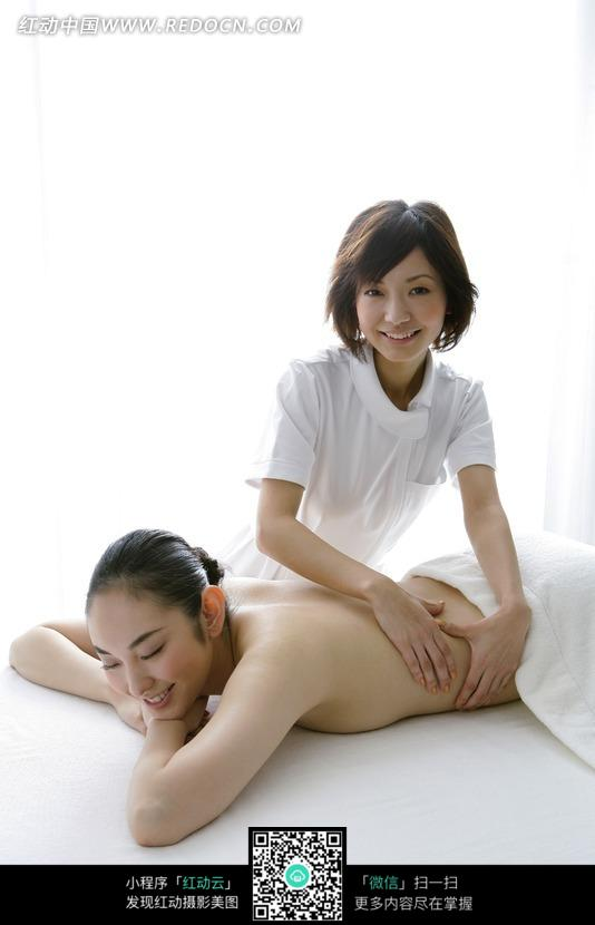 按摩美女腰部的按摩师图片