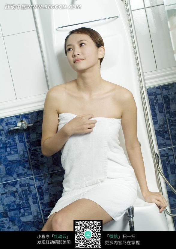 裹着浴巾坐在浴室里的美女图片