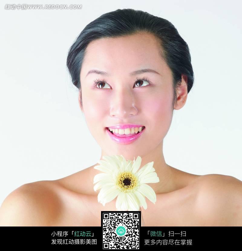 双手夹子一朵白色菊花的女人
