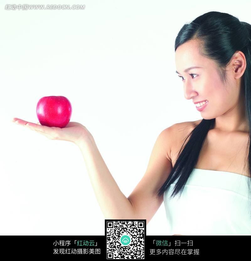 侧身盯着手上红苹果的美女图片