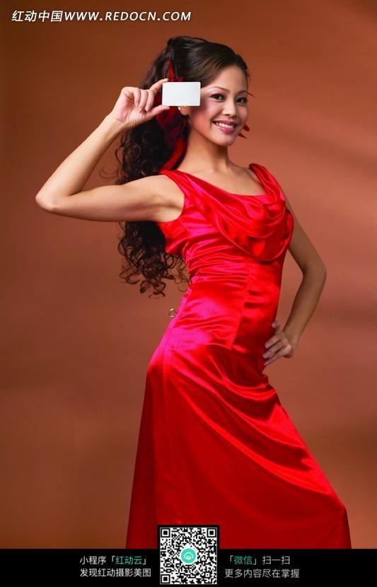 拿着空白名片的红衣美女图片