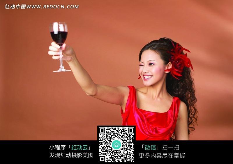 右手举着红酒杯闭一只眼睛的女人图片