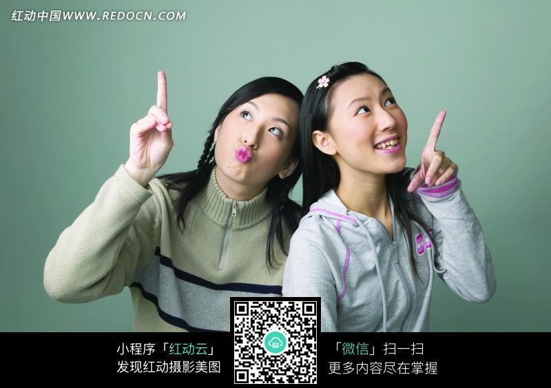 两个指向上方的快乐女孩图片