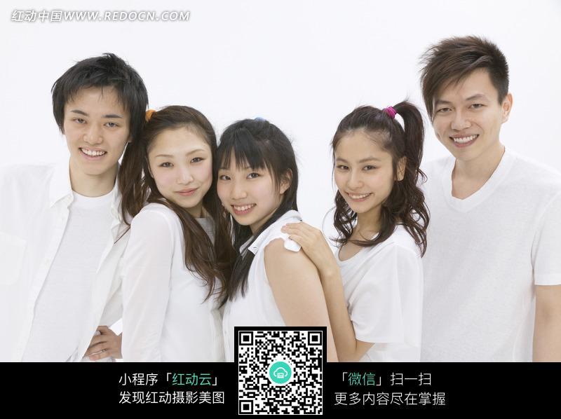 一群靠在一起的微笑的年轻人图片