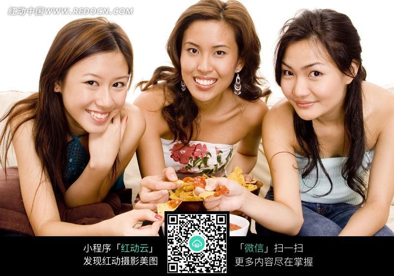 三个坐在沙发上吃东西的女子图片