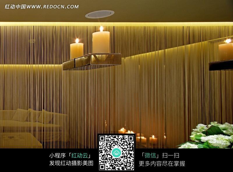玻璃窗前架子上的两个点燃的蜡烛图片