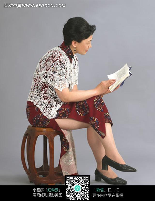 圆凳上坐着看书的女人