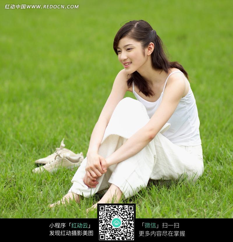 赤脚坐在绿草地上微笑的美女图片