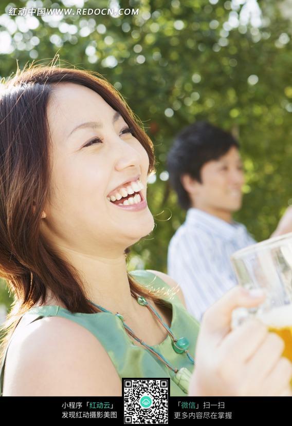 室外端着啤酒杯开心大笑的美女图片 日常生活