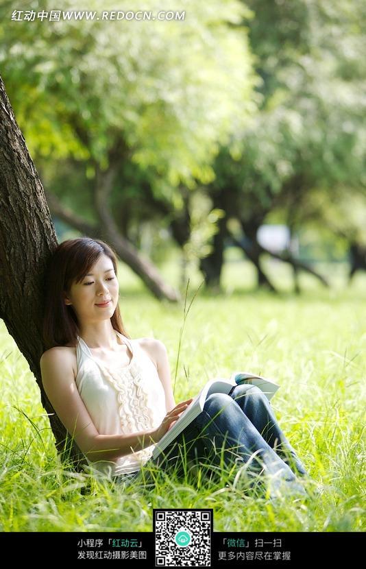 靠在树木下看书的美女图片