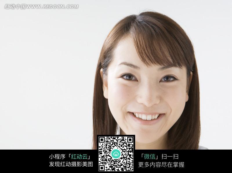 微笑的长发女人的脸部特写图片