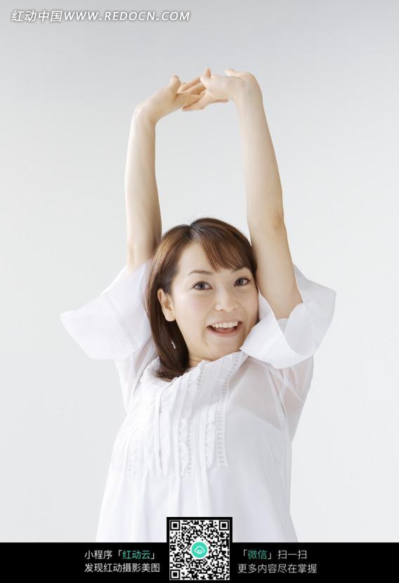 美女/双手举在头顶上微笑的白衣美女