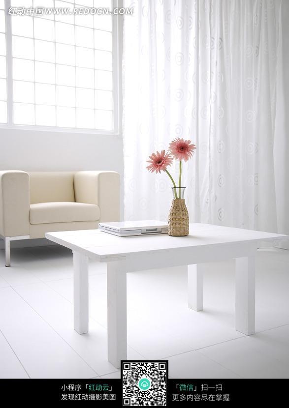 放着电脑与花瓶的白木桌和远处的沙发图片