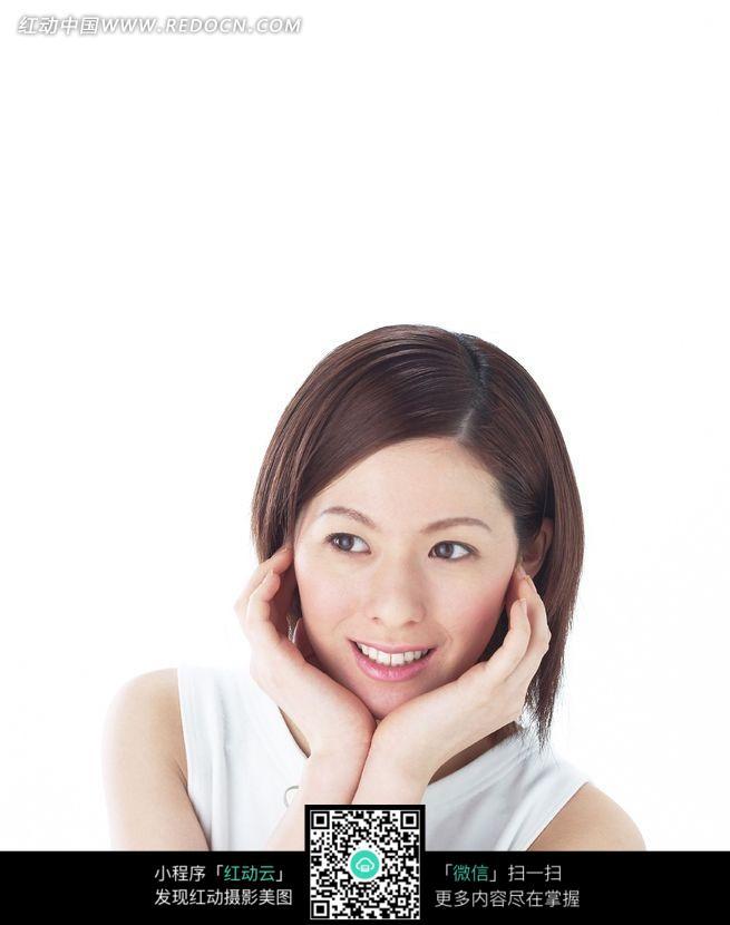 双手捧着脸微笑的短发美女图片