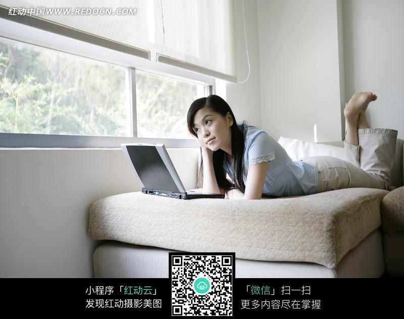 趴在窗边床上玩电脑的美女图片