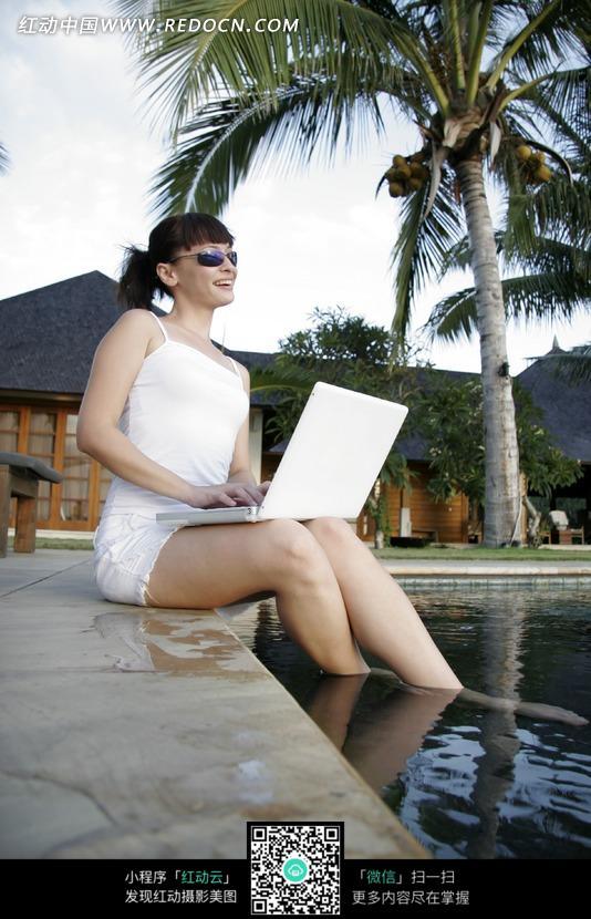 戴墨镜坐在浴池边玩电脑的美女图片 日常生活