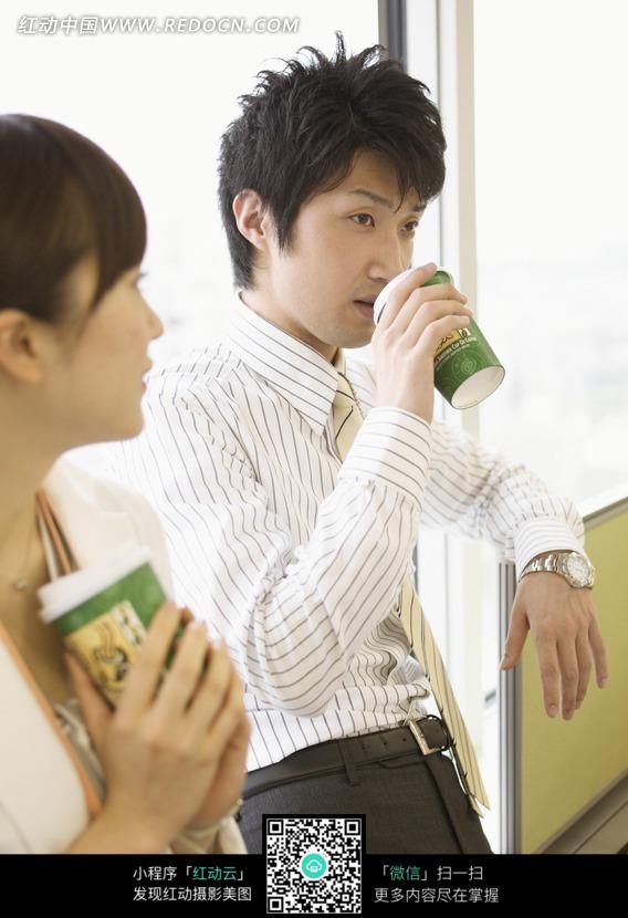 靠窗户喝饮料的职场帅哥图片