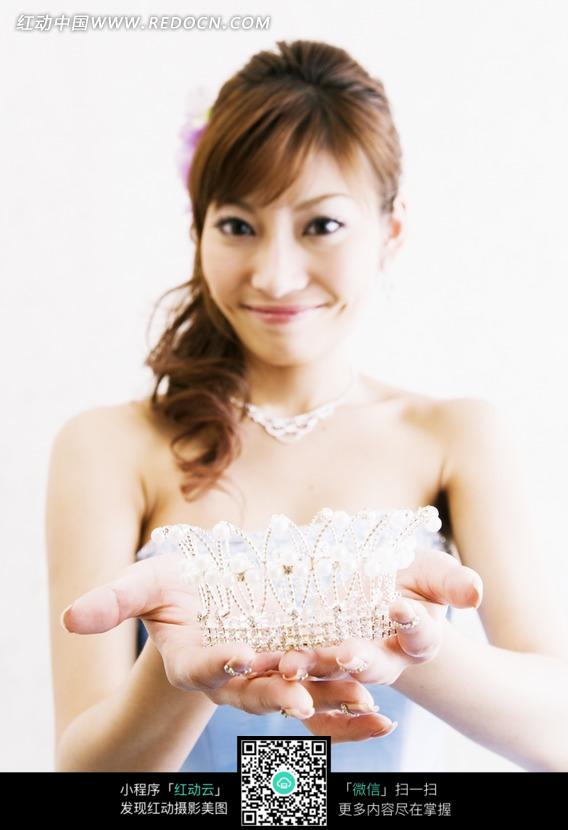 微笑着手捧皇冠的美女
