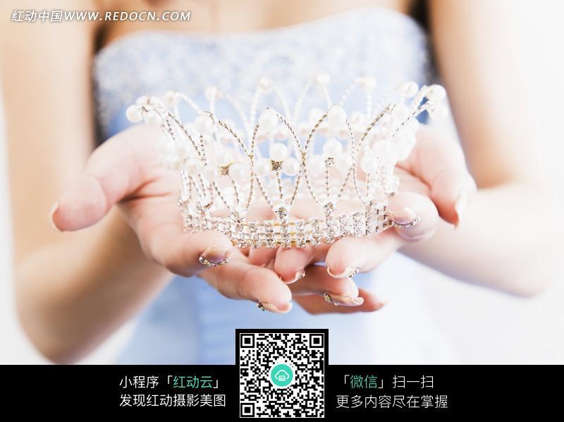 美女手捧着的珍珠皇冠