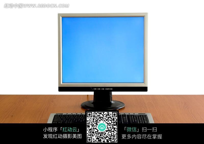 桌子上的电脑显示屏和键盘