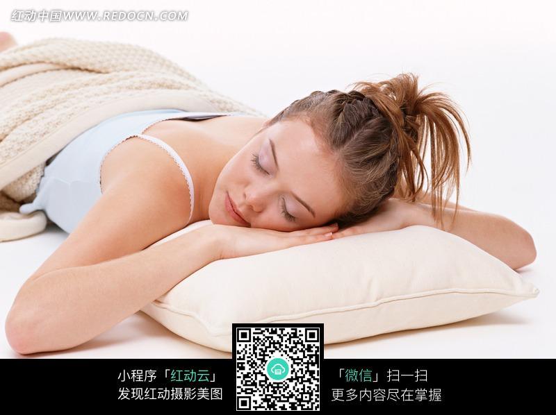 趴在白色抱枕上睡觉的外国美女图片