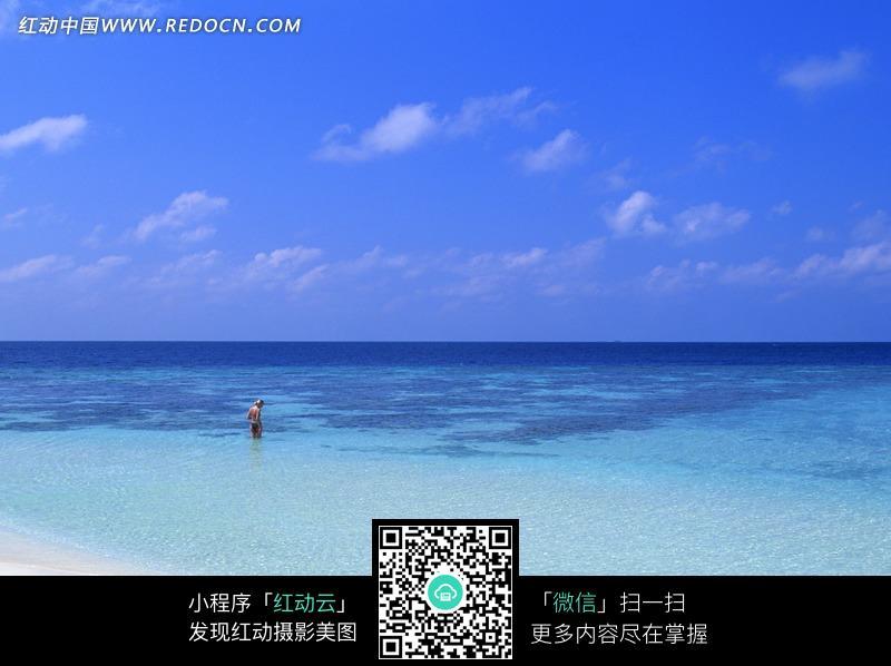 蓝天白云下沙滩海水上的比基尼美女图片
