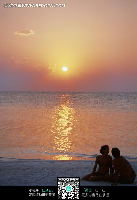 夕阳下坐在海边沙滩上的两个人