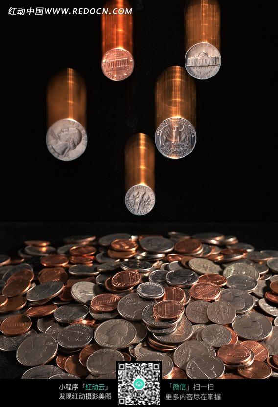 一堆硬币和正在掉落的五枚硬币