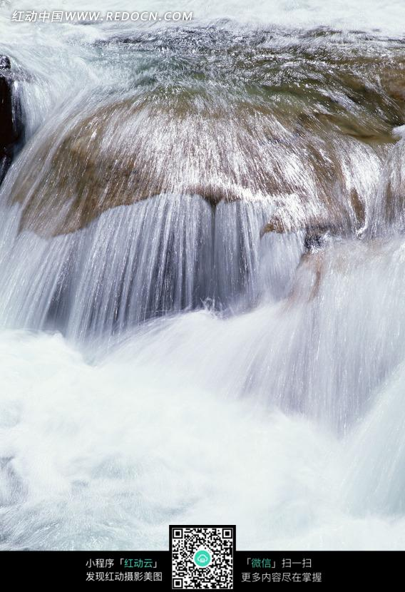 石头上流淌溪水激起的白色水花