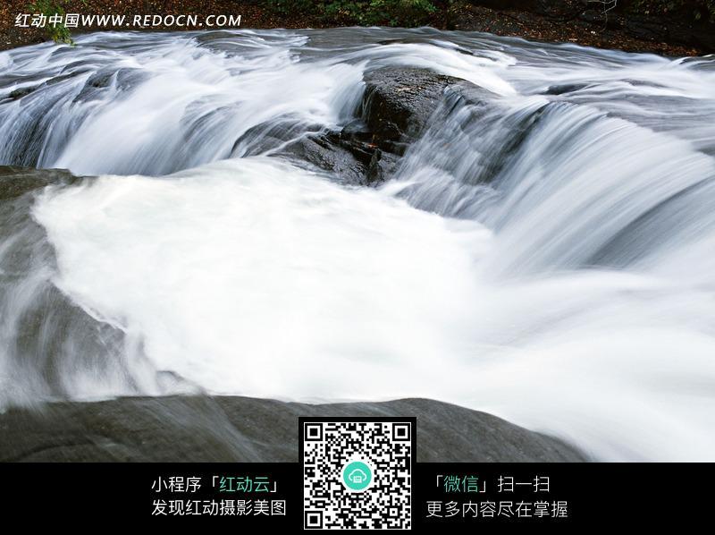 石头上流淌的白布一样的溪水图片