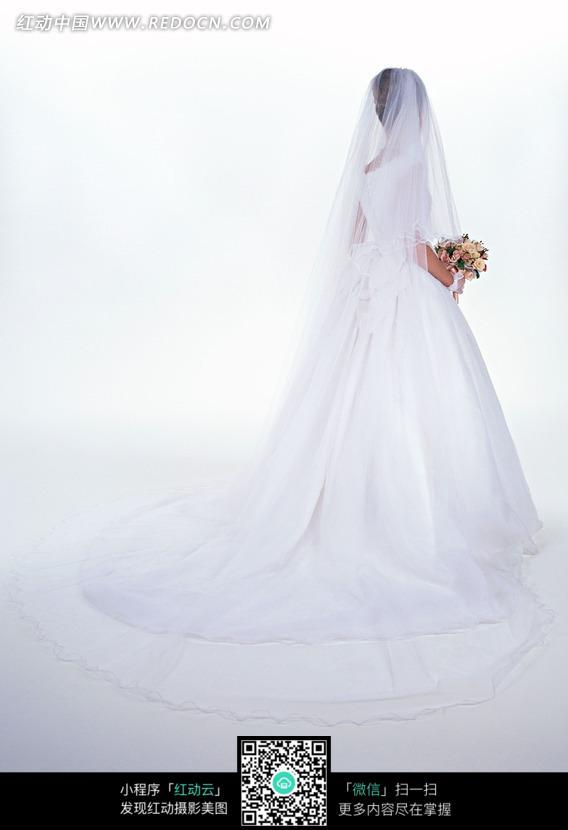 拿着捧花穿白色婚纱的女人背影
