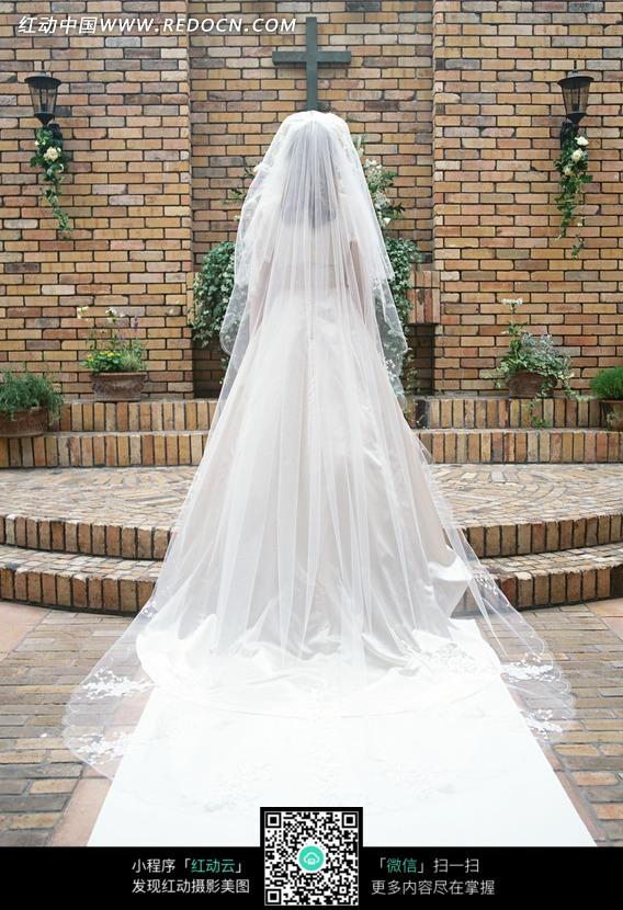 十字架下一个穿着白色婚纱的女人背影