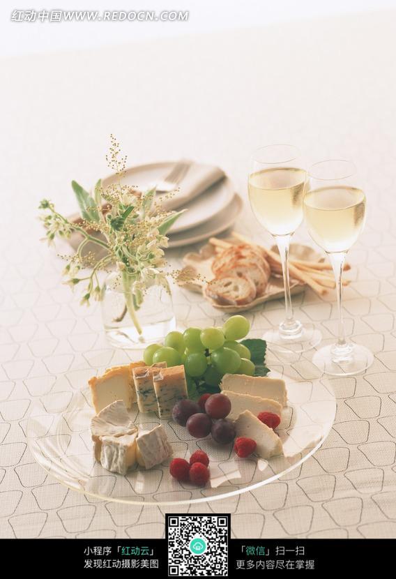 暗格桌子上放在盘子里的水果糕点和鲜花高脚杯图片