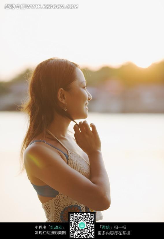 海边手夹发梢微笑的美女侧影