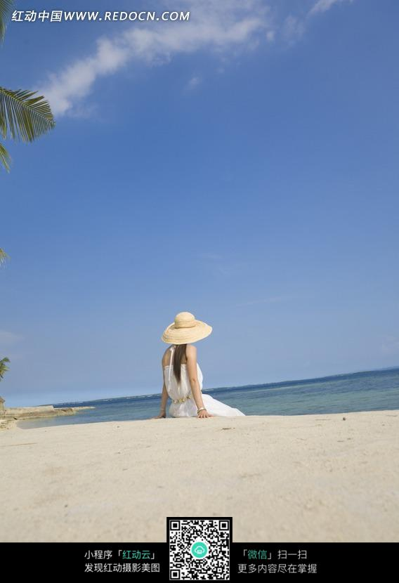 海边沙滩上戴着帽子的美女背影图片