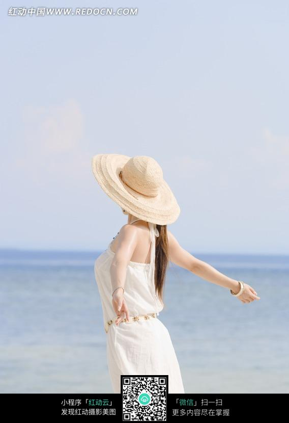 海边美女飞翔姿式的背影图片