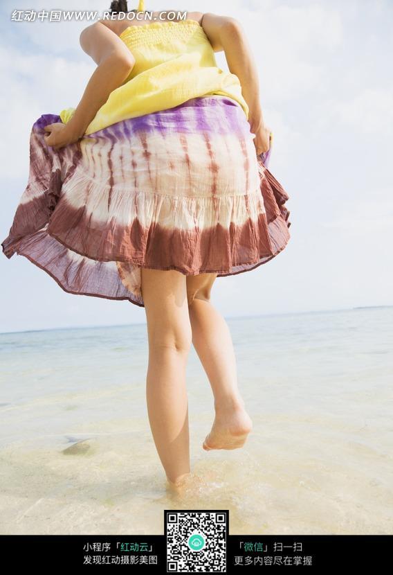 海边踏水的女孩背影