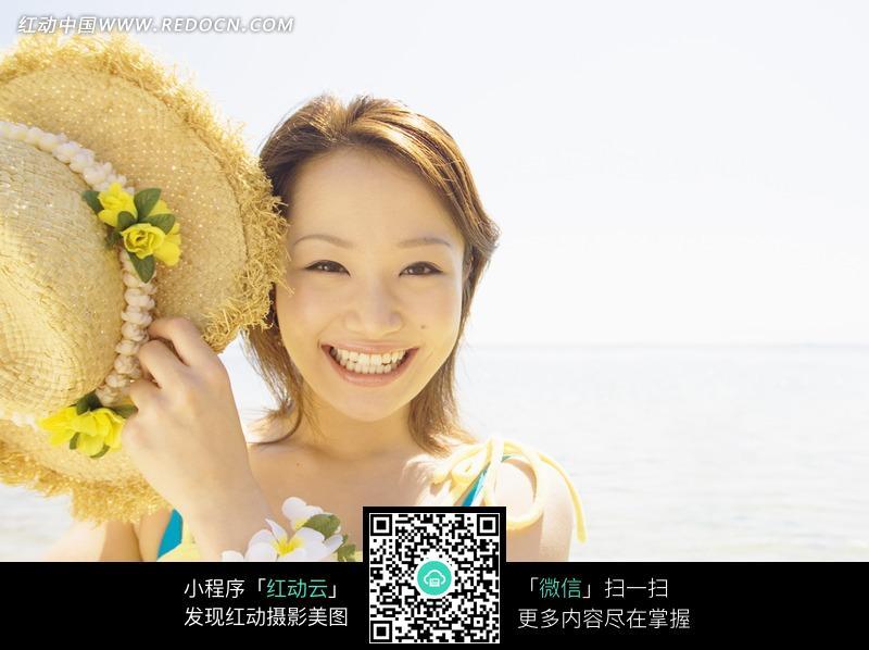 海边手托帽子的美女图片