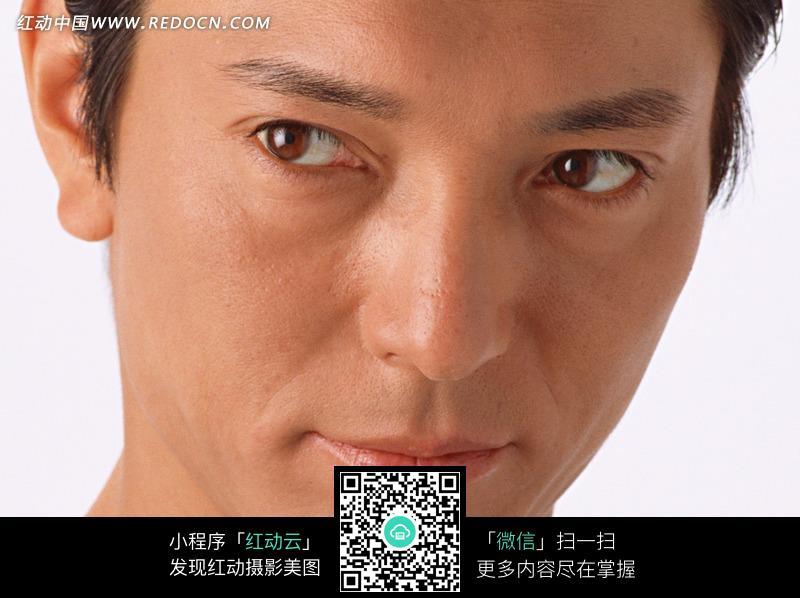 斜视前方的男人的脸部特写图片