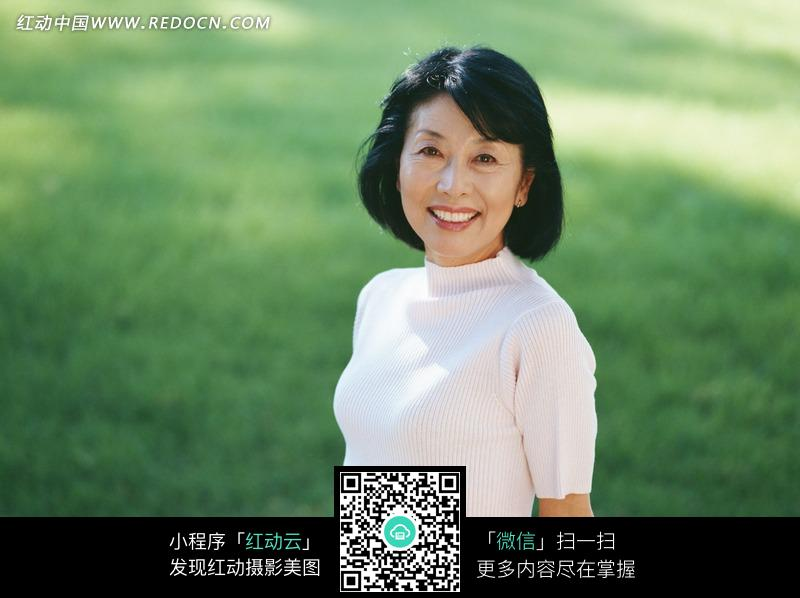 草地上微笑的中年女人图片