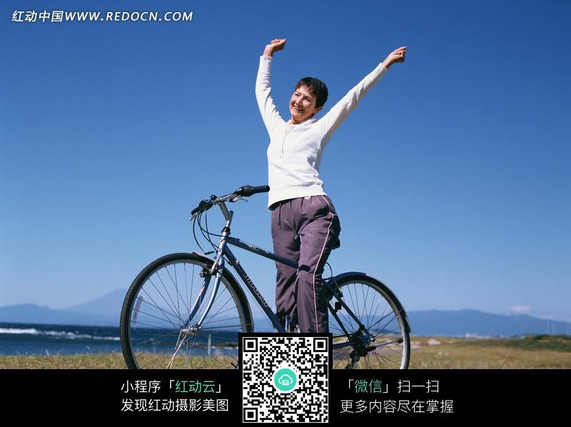 蓝天草地上骑自行车的女人图片图片