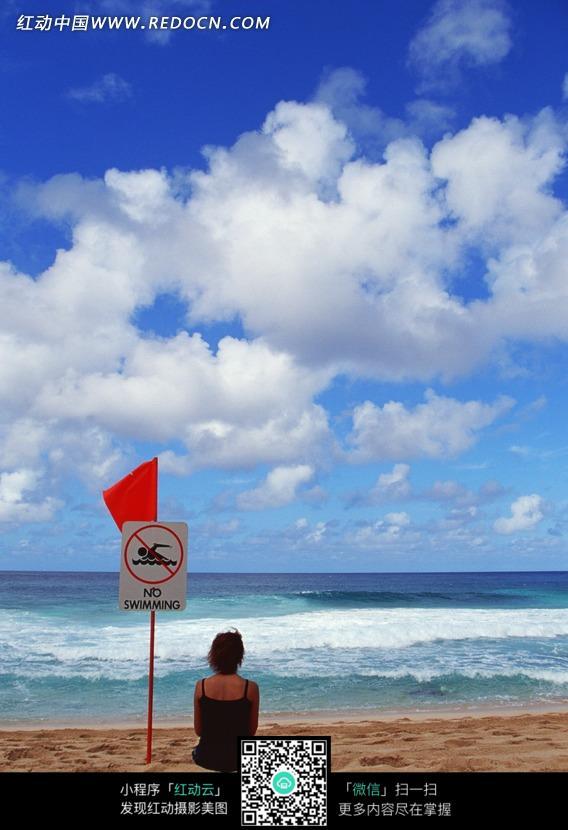 蓝天白云下坐在海边沙滩上告示牌旁的女人