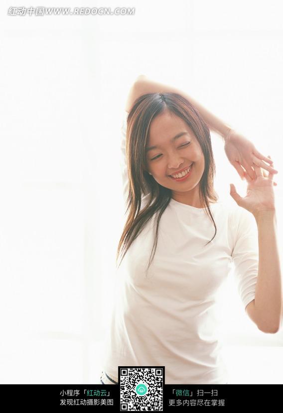 微笑着活动筋骨的长发美女图片