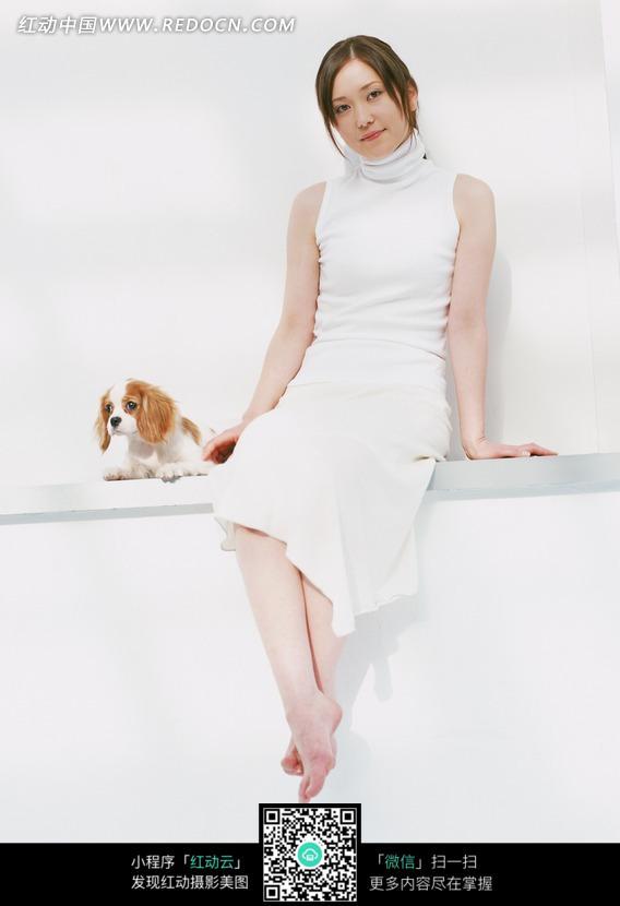 和可爱小狗坐着一起的白衣美女