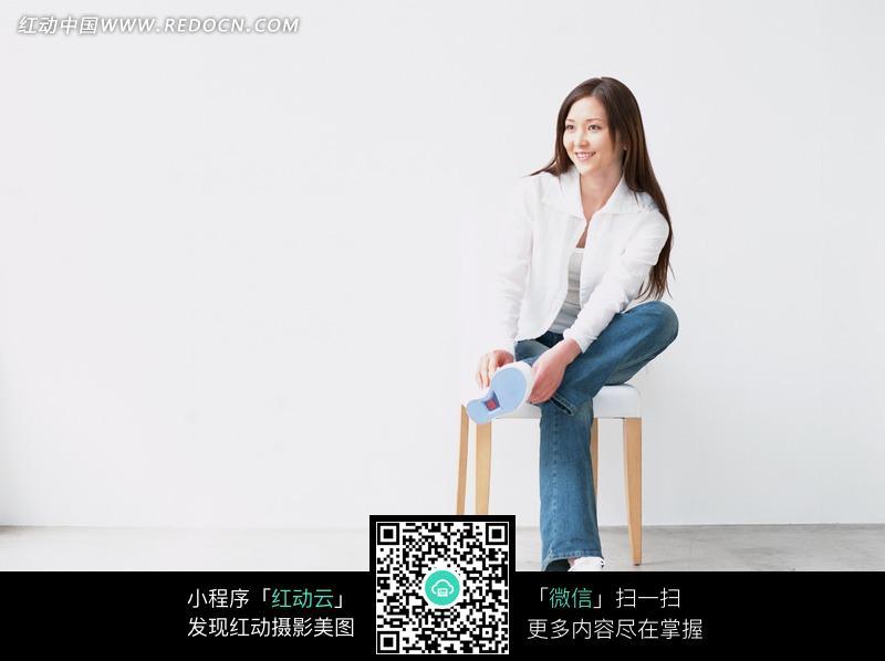 坐在凳子上跷二郎腿的长发美女图片