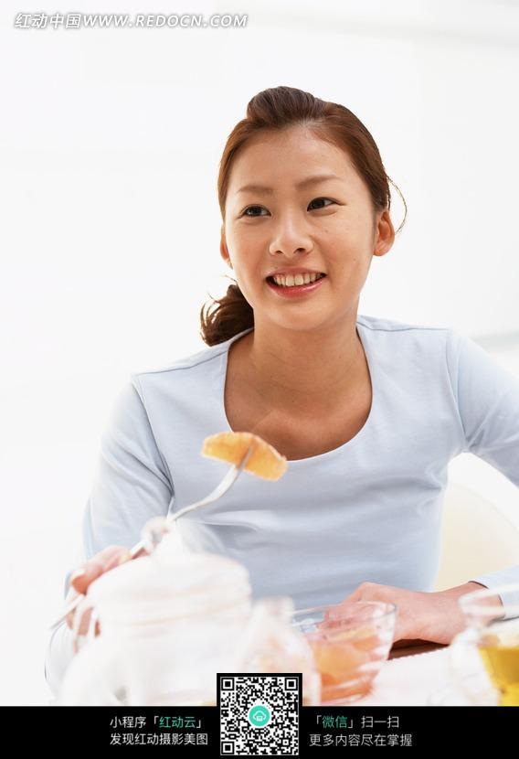 水果前叉着女人v水果的美女图片_餐桌图片女性美女白裤绿衣图片