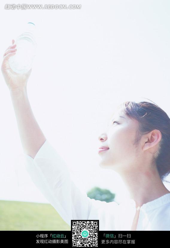 素材下载 图片素材 人物图片 女性女人 > 草地阳光下举着瓶子的美女